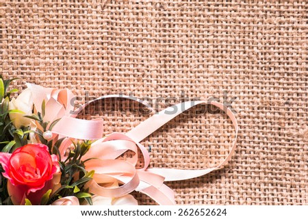 Arrangement of artificial flowers located on burlap background, closeup, useful as background, wedding invitation and greeting card