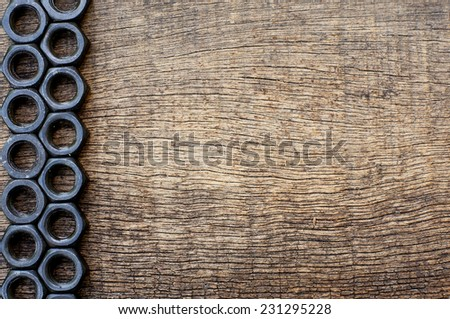 arrangement of black nut on the side on an old cracked wooden background - stock photo