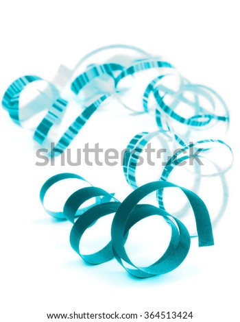 Arrangement of Blue and Striped Curled Party Streamers Lying on white background. Focus on Foreground - stock photo