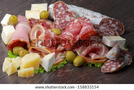 Arrangement of Delicatessen Cold Cuts with Smoked Ham, Pepperoni, Salami, Finocchiona, Green Olives, Grana Padano and Camembert Cheese closeup on Dark Wooden background - stock photo