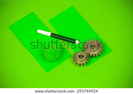 Arrangement of double cog wheel element with vibrant cards and whiting marker, showing funny playful approach to mechanical dynamics theoretical sciences and heavy machine industry terms and items - stock photo