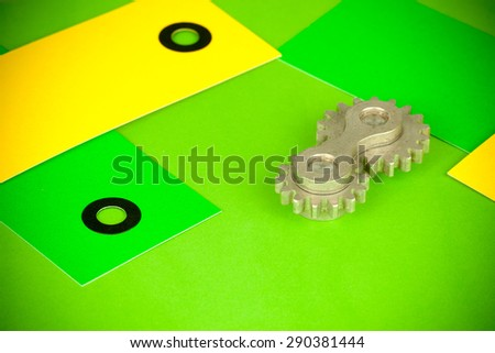Arrangement of double cog wheel element with yellow and green cards, showing funny vibrant saturated approach to mechanical dynamics theoretical sciences as wells as to heavy machine industry terms - stock photo
