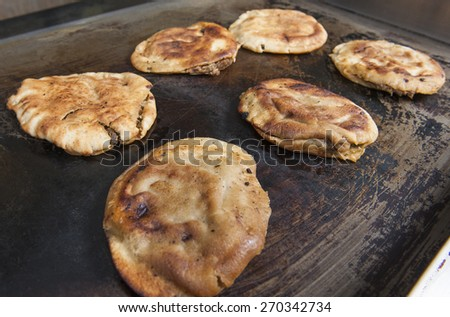 Arrangement of egyptian hawawshi being cooked at an oriental restaurant buffet - stock photo
