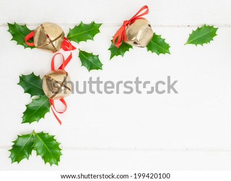 arrangement of holly leaves  with sleigh bells against a rustic white table top - stock photo
