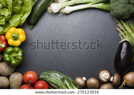 Arrangement of mixed colorful vegetables, isolated on dark gray slate stone background with empty copy space. - stock photo