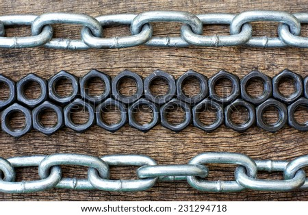 arrangement of nuts bolts and iron chains in old cracked wooden background - stock photo