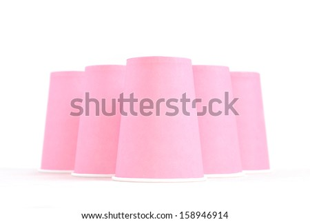 Arrangement of pink recycling paper glasses on white background