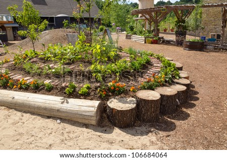 Arrangement of plants and logs in circular bed - stock photo