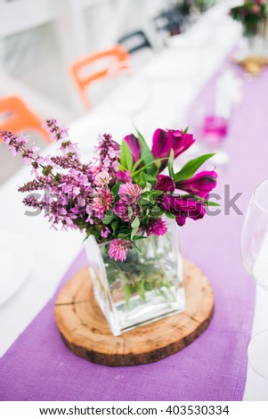 Arrangement of purple wild flowers standing on the wedding table in a glass vase. Wedding in summer pergola. On the table a white tablecloth and a purple path on the chairs background - stock photo