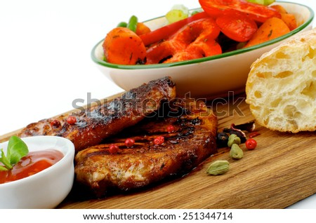 Arrangement of Roasted Pork Steaks with Grilled Vegetables, Tomato Sauce and Bread on Wooden Plate closeup on white background - stock photo