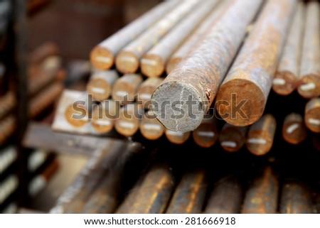Arrangement of rust steel bars in warehouse - stock photo