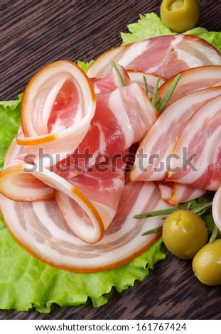 Arrangement of Smoked Ham Slices with Green Olives on Lettuce Leaves closeup on Dark Wooden background - stock photo