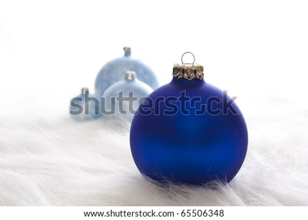 Arrangement of some blue christmas baubles on white fur - stock photo