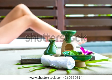 Arrangement of spa treatment products made out of massage oil and towel by poolside with pair of woman's leg in background. - stock photo