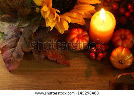 Arrangement of sunflower, candle and autumn decorations on wooden background with copy space. - stock photo