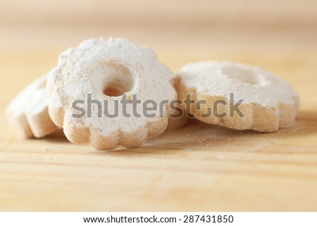 Arrangement of three italian butter cookies on a wooden table. Canestrelli biscuits are a regional receipt from Liguria and Piedmont - stock photo