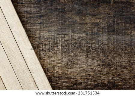 arrangement of wooden sticks in the bottom corner on the old wooden background - stock photo