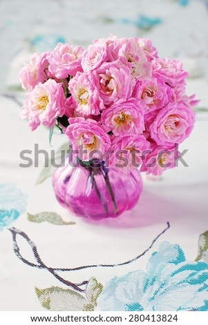 Arrangement with a fresh pink roses on a table. - stock photo