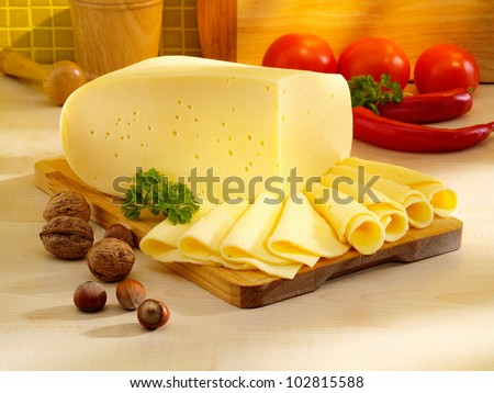 Arrangement with appetizing cheese on the kitchen cutting board. - stock photo