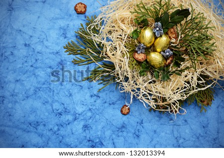 Arrangement with eggs and nest in the corner on a blue background - stock photo