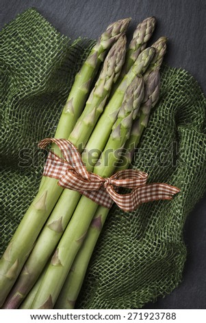 Arrangement with tied bunch of asparagus and green cloth, on dark grey slate stone background. - stock photo