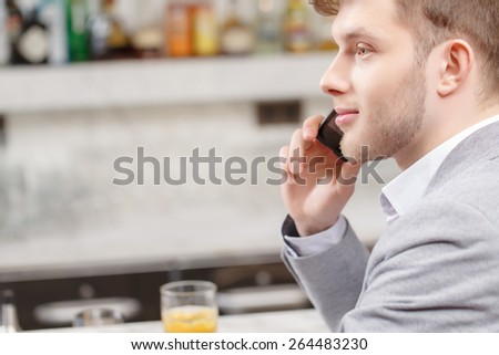 Arranging a meeting in the bar. Close-up of a young handsome man talking over the phone while sitting at the counter of the bar - stock photo