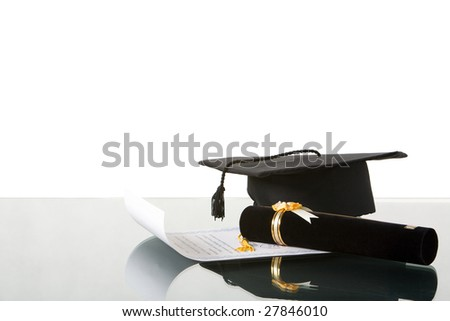 Arranging graduation tassel on the desk against white background - stock photo