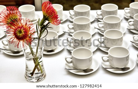 Array of empty tea/coffee cups and flower vase on white table. Shot on 8/07 in Stellenbosch, Western Cape, South Africa. - stock photo