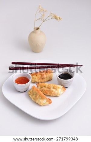 Array of fried Chinese pot stickers on white plate with ceramic pots of chili & soy dipping sauces with dark wood chopsticks & clay vase with baby's breath in the background - stock photo