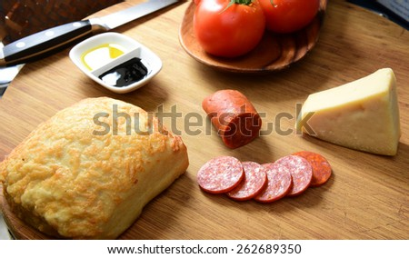 Array of parmesan & mozzarella cheeses with ciabatta, pepperoni, olive oil, balsamic vinegar, fresh tomato & ciabatta loaf on cutting board with knife in background - stock photo