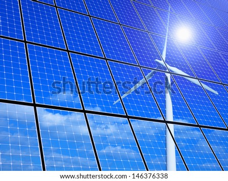 Array of solar panels with wind turbine reflection  - stock photo