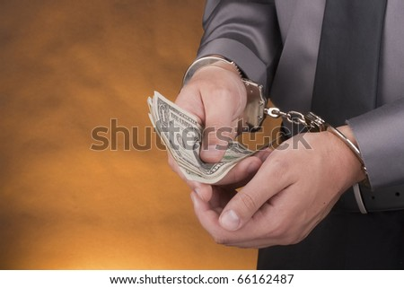 Arrest, close-up man's hands with money in handcuffs. - stock photo