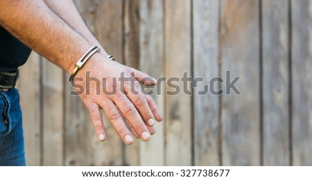 Arrest, close-up shot man's hands with handcuffs in front of plank wood  wall with copy-space