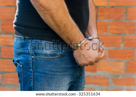 Arrest, close-up shot man's hands with handcuffs in front of terracotta brick blocks wall, right hand side - stock photo