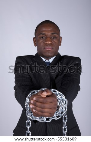 Arrested african businessman with a steel chain in his hands - stock photo