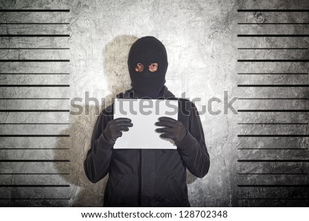 Arrested burglar. Thief with balaclava caught and arrested in front of the grunge concrete wall. - stock photo