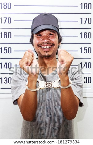 Arrested Man with handcuffs taking criminal mug shot - stock photo