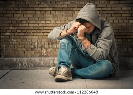 Arrested teenager with handcuffs on his hands - stock photo
