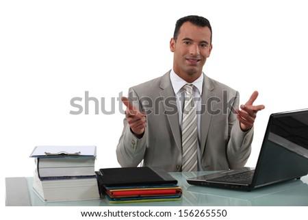Arrogant businessman sat at desk - stock photo