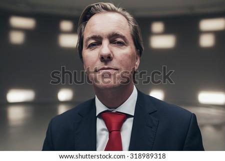 Arrogant entrepreneur wearing suit with red tie in empty room. - stock photo