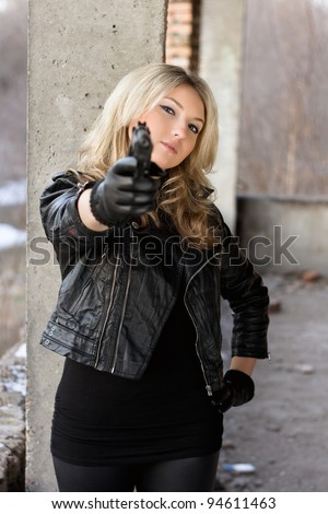 Arrogant young woman in leather jacket with a gun - stock photo