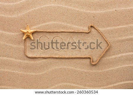 Arrow made of rope and sea shells with the word Goa on the sand, as background  - stock photo