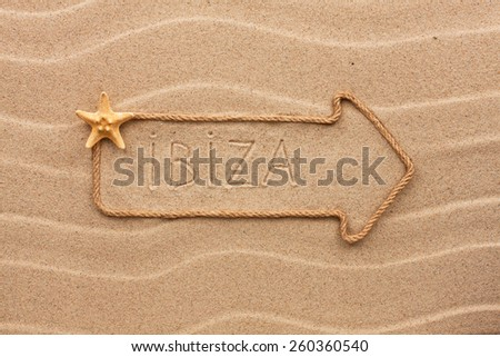 Arrow made of rope and sea shells with the word Ibiza on the sand, as background  - stock photo