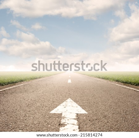 arrow on asphalt road to the horizon - stock photo
