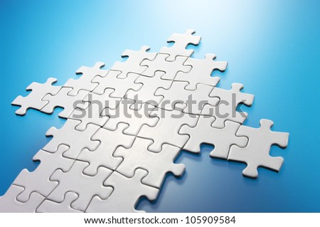 Arrow shaped jigsaw puzzle. Concept image of growth,success and building a business. - stock photo