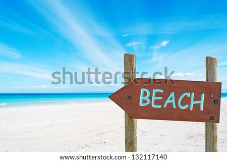 arrow-shaped wooden sign at the beach - stock photo