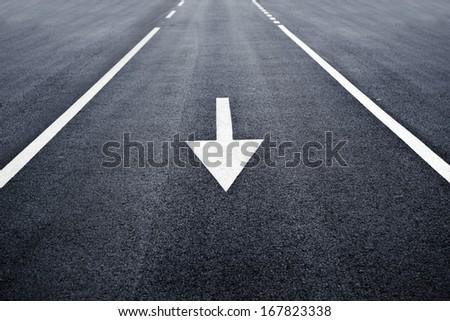 Arrow sign on asphalt surface. Arrow sign on highway road. - stock photo