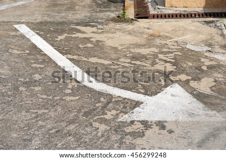 arrow sign on surface of street - stock photo