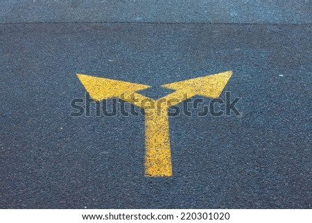 Arrow sign on the asphalt road - stock photo