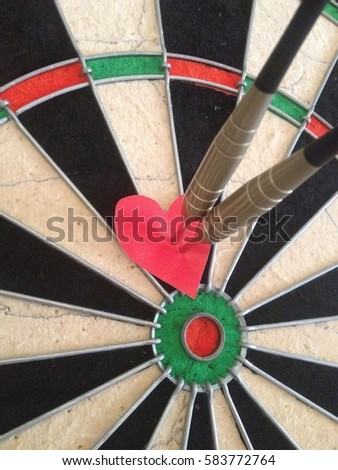 Arrow through a love heart on a dart board